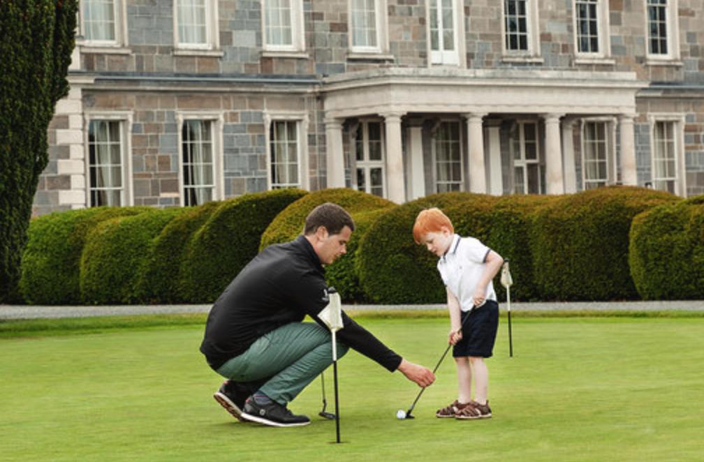 Dad & son play golf putting green